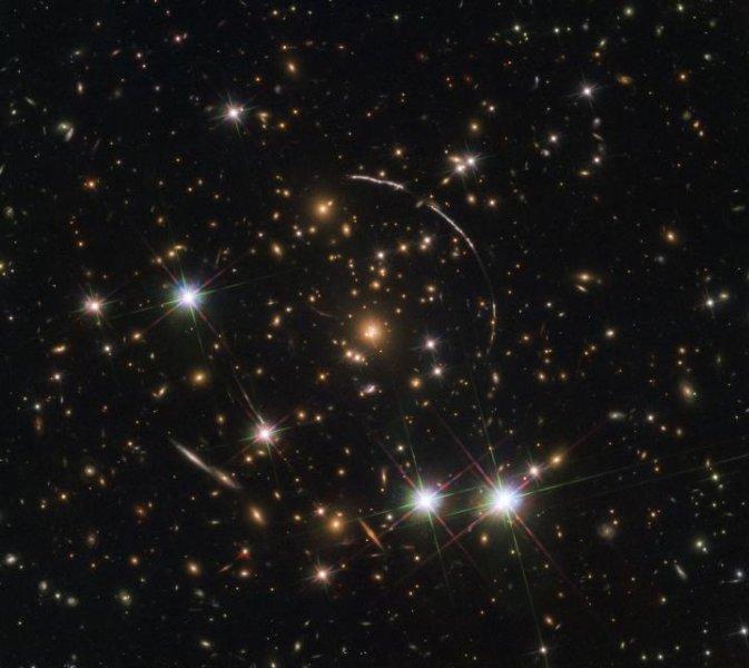 На этом снимке, снятом космическим телескопом Хаббла НАСА / ЕКА, показано массивное скопление галактик, расположенное на расстоянии около 4,6 миллиарда световых лет. Вдоль его границ видны четыре яркие дуги; это копии той же далекой галактики, по прозвищу Арка Солнечных лучей. Предоставлено: ESA / Hubble, NASA, Rivera-Thorsen et al.
